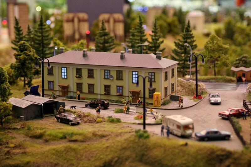 Гранд макет: старый жёлтый кирпичный дом в посёлке. гаражи, мусорный контейнер, телефонная будка, отдахующие на лавочках жители