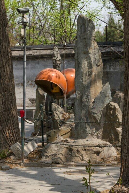 Камень и телефонная будка в монастырском саду, храм Белого облака, Пекин