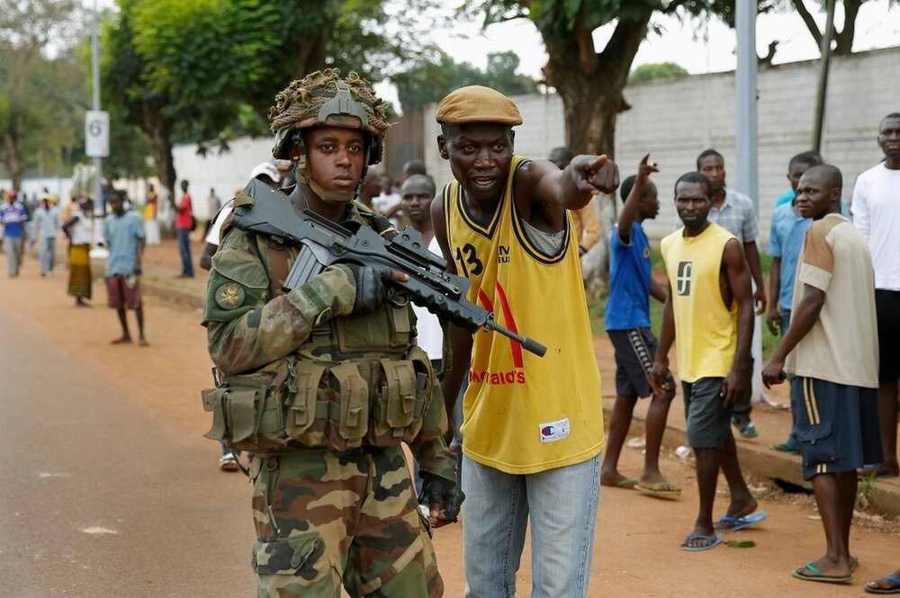 Местный житель указывает солдату из многонациональных сил по поддержанию порядка в Центральной Африке на представителя мусульманской Seleka, который пытается затеряться в людской толпе