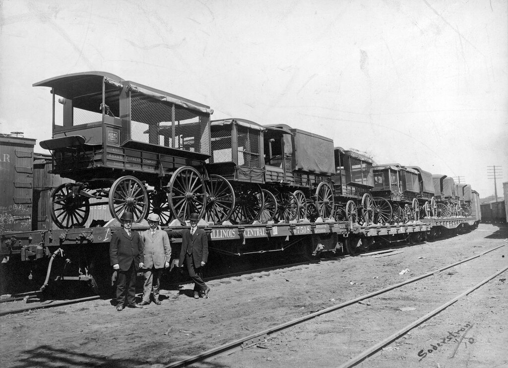 The cars are loaded with wagons belonging to the Adams Express Company, Denver, Colorado, between 1890 and 1910