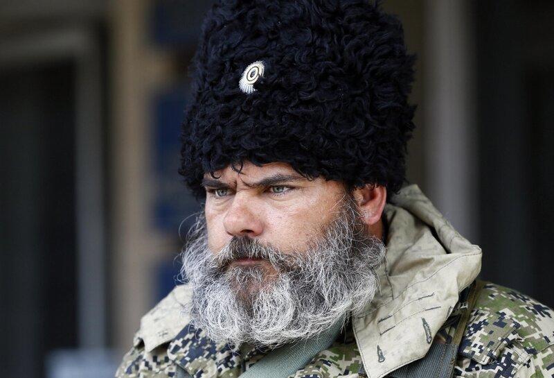A pro-Russian armed man looks on near the mayor's office in Slaviansk