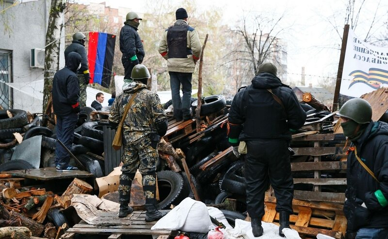 Pro-Russian men stand guard at a barricade near the police headquarters in Slaviansk April 13, 2014. Ukraine's Interior Minister on Sunday told residents in the eastern city of Slaviansk to stay indoors, in anticipation of clashes between pro-Russian mili