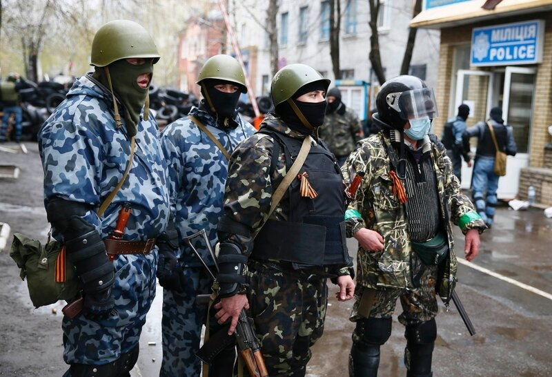 Pro-Russian armed men stand guard while pro-Russian protesters gather near the police headquarters while a military helicopter (not pictured) flies above, in Slaviansk April 13, 2014. Ukraine's Interior Minister on Sunday told residents in the eastern cit