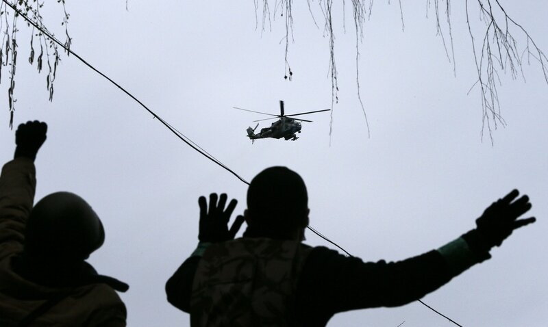 People gesture while pro-Russian protesters gather at the police headquarters, with a military helicopter flying above, in Slaviansk