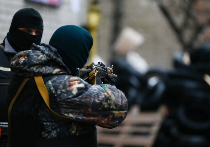 A pro-Russian armed man checks the gun sight of his weapon next to a barricade in front of the police headquarters in Slaviansk April 13, 2014. Ukraine's Interior Minister on Sunday told residents in the eastern city of Slaviansk to stay indoors, in antic