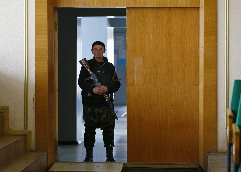 A pro-Russian armed man stands guard at the mayor's office in Slaviansk