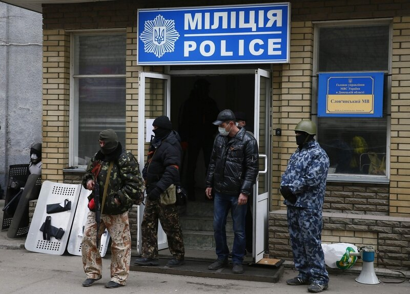 Armed men stand in front of the police headquarters building in Slaviansk