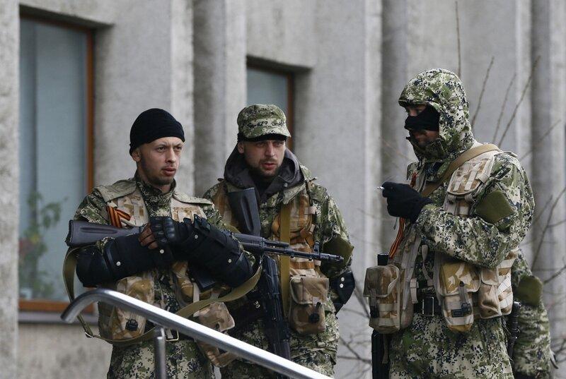 Pro-Russian armed men stand guard outside the mayor's office in Slaviansk