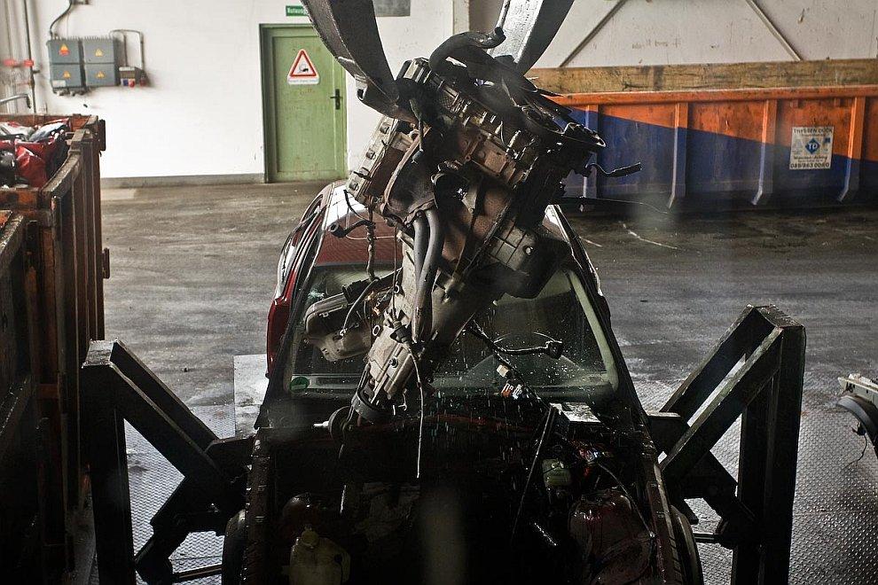 Поверженный и почти уничтоженный автомобиль уложен в прокрустово ложе пресса. Сейчас верхняя крышка