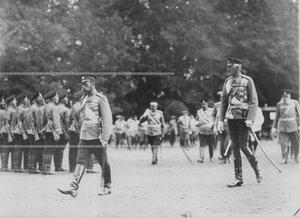 Император Николай II и великий князь Николай Николаевич в сопровождении свиты обходят подразделения полка.