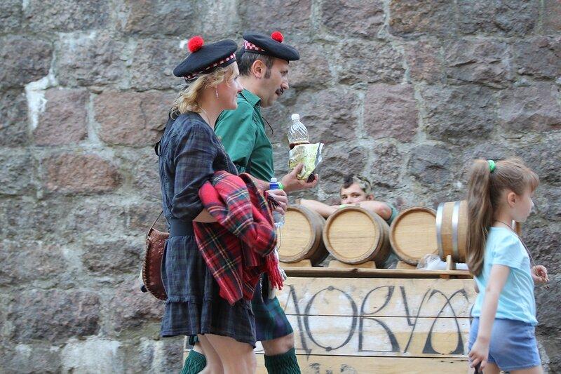 шотландская пара в беретах с красными помпонами на фоне бочек с медовухой - фестиваль «Майское дерево 2014»