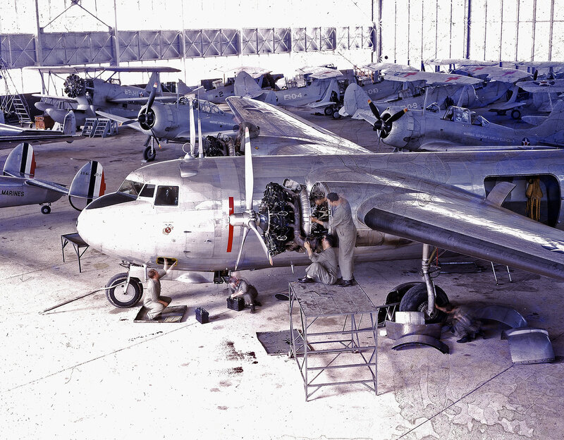 Partial left side view of the front half of U.S. Marine Corps Douglas R3D-2 having its left engine worked on by two mechanics and front langing gear worked on by two others; the aircraft is inside a hangar and there are many other U.S. Marine Corps aircra