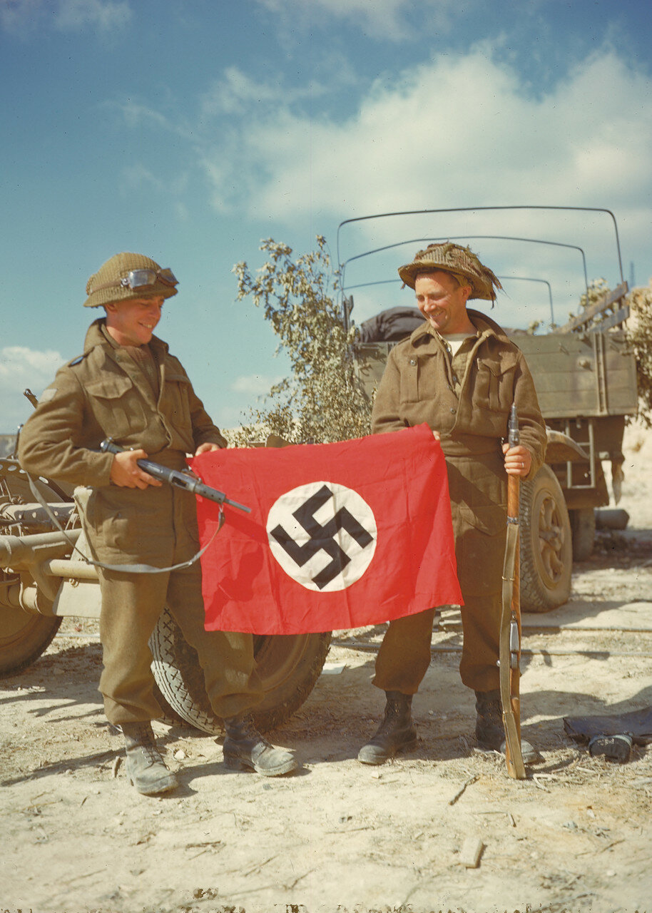 23. Канадские солдаты с захваченным фашистским флагом