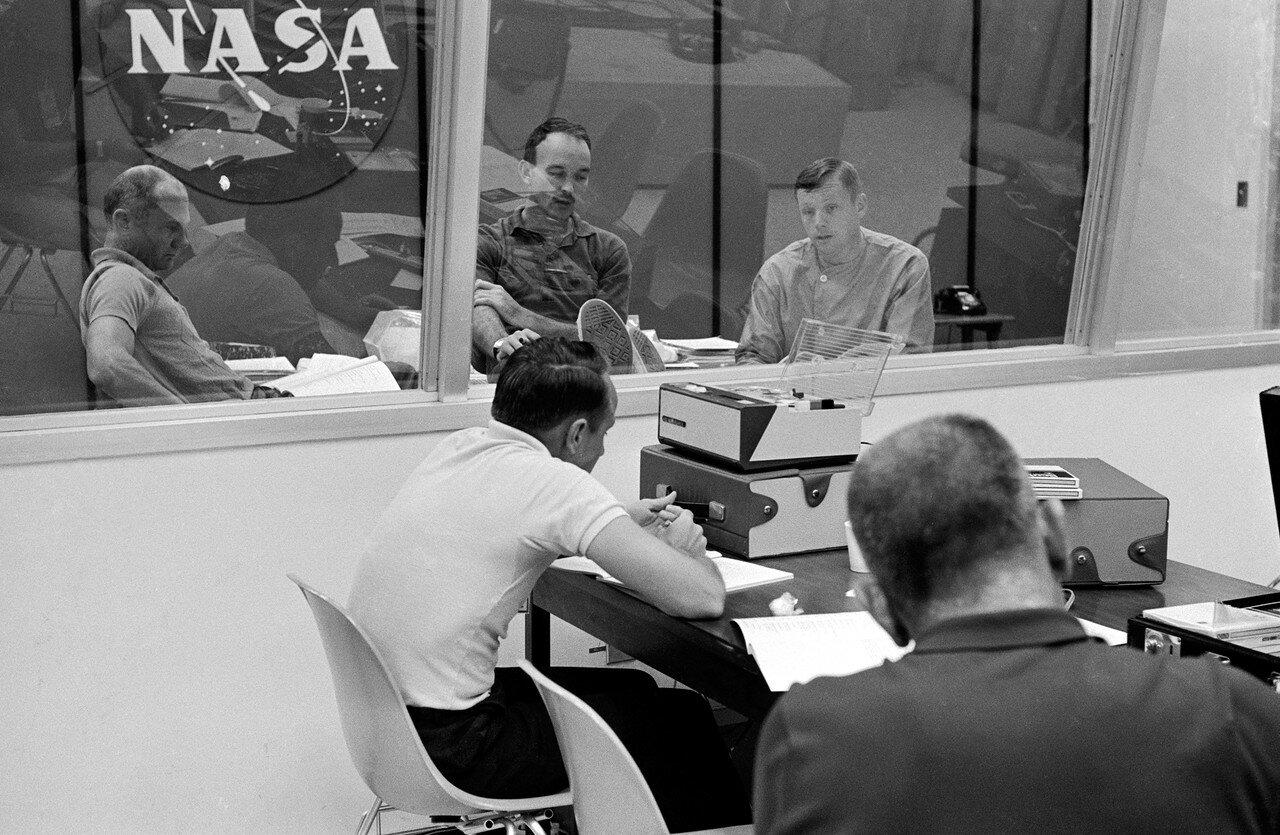 Астронавты должны были находиться в карантине 21 день (считая с момента старта с Луны). На снимке: За стеклянной стеной слева направо. Олдрин, Коллинз и Армстронг во время послеполётного опроса в Лунной приёмной лаборатории (ЛПЛ)