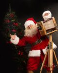 Santa Claus taking picture with old wooden camera standing near Christmas tree at home