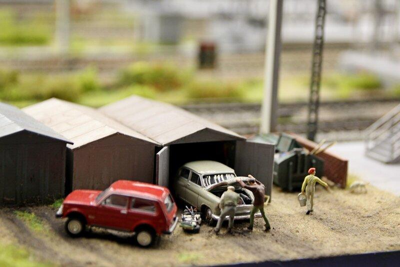 Гранд макет: гаражи. Мужики чинят старую Победу. Рядом стоит красная Нива.