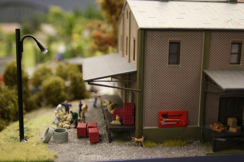 Гранд макет: склады. Гравийная дорожка, пожарный щит на кирпичной стене, собака задрала заднюю лапу на угол дома.