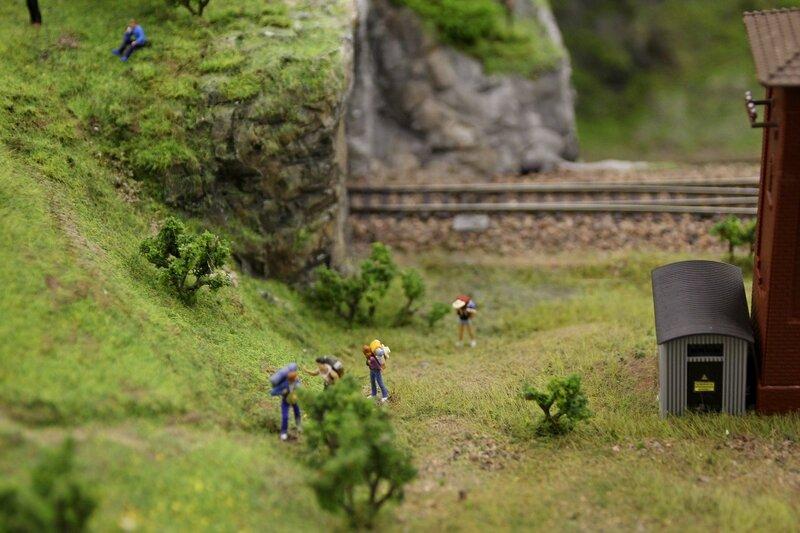 Гранд макет: туристы с рюкзаками поднимаются по тропинке в гору рядом с железнодорожным тоннелем
