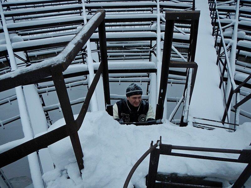 Лёшка залазит по лестнице на верх недостроенной градирни
