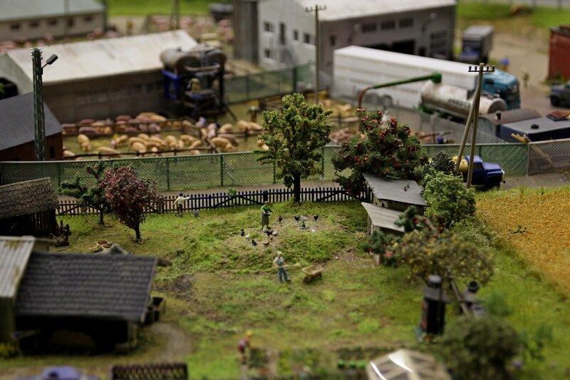 Гранд макет: деревенское подворье - женщина кормит птиц, мужчина что-то нагребает в тачку лопатой, на яблоне созрели красные яблоки, на заднем фоне скотный двор и свиньи в загонах