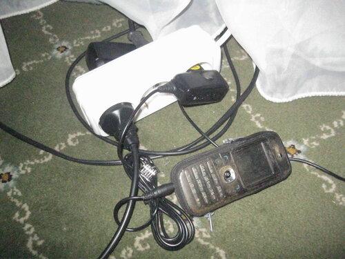 Фото 1. Мобильный телефон заряжается. Зарядное устройство подключено к электросети через удлинитель с двусторонней колодкой.
