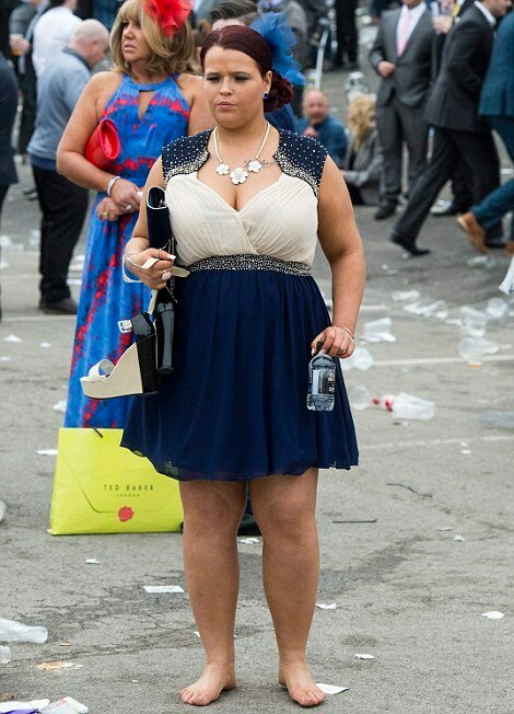 Barefooted and carrying a bottle of water, this racegoer starts to make her way home at Ladies Day, Aintree Racecourse, The Crabbies Grand National