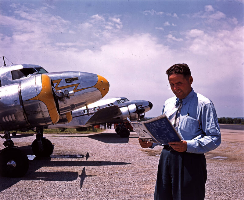 A man standing in front of two Lockheed Model 12A Electra Junior aircraft, belonging to the Oil Country Services Manufacturing Company and the Superior Oil Company, at William P. Hobby Airport in Houston, Texas. March 1940