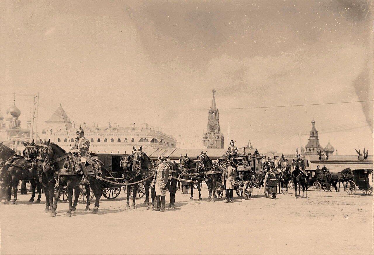 Военные и гражданские чины, дворцовые служащие у карет и экипажей участников торжественной коронации в Кремле; на втором планеслева-часть фасада Малого Николаевского дворца,в центре - Спасская башня