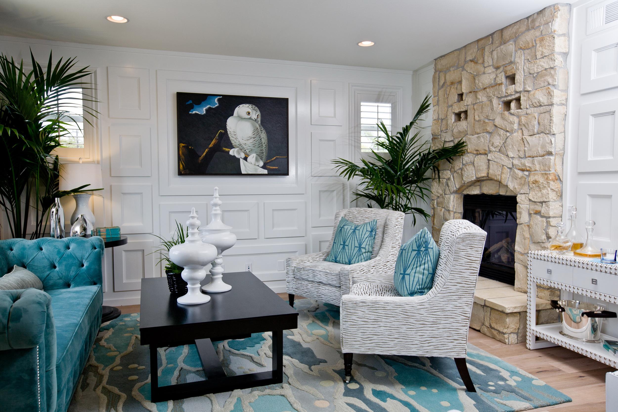 гостиная в бело-бирюзовых тонах, черный стол, белые кресла, синий диван, камин
