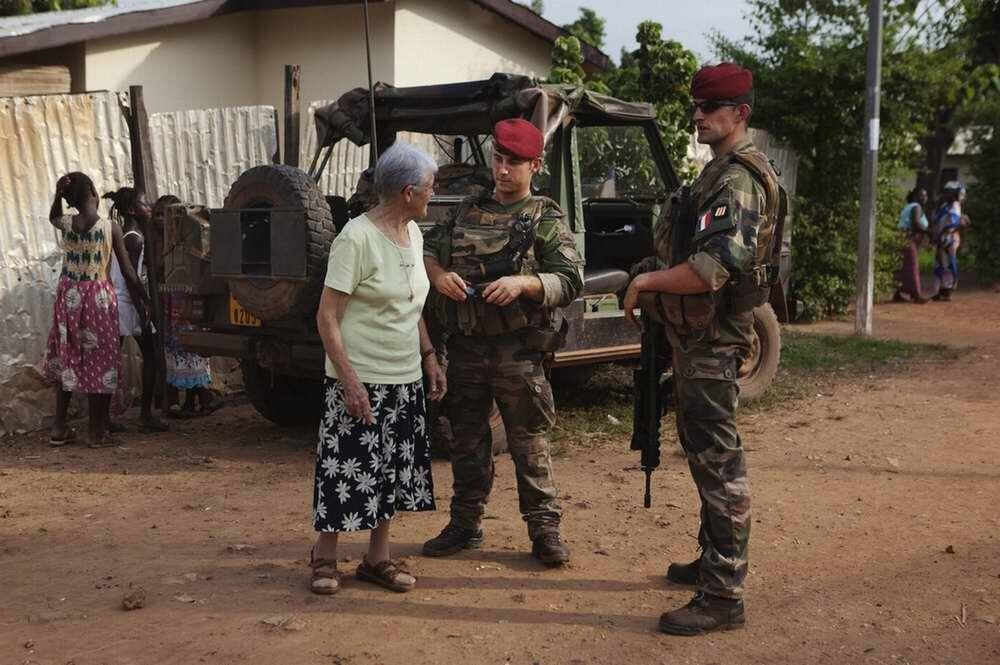 Патрульные солдаты беседуют с белой французской монахиней, которую они встретили у себя на пути