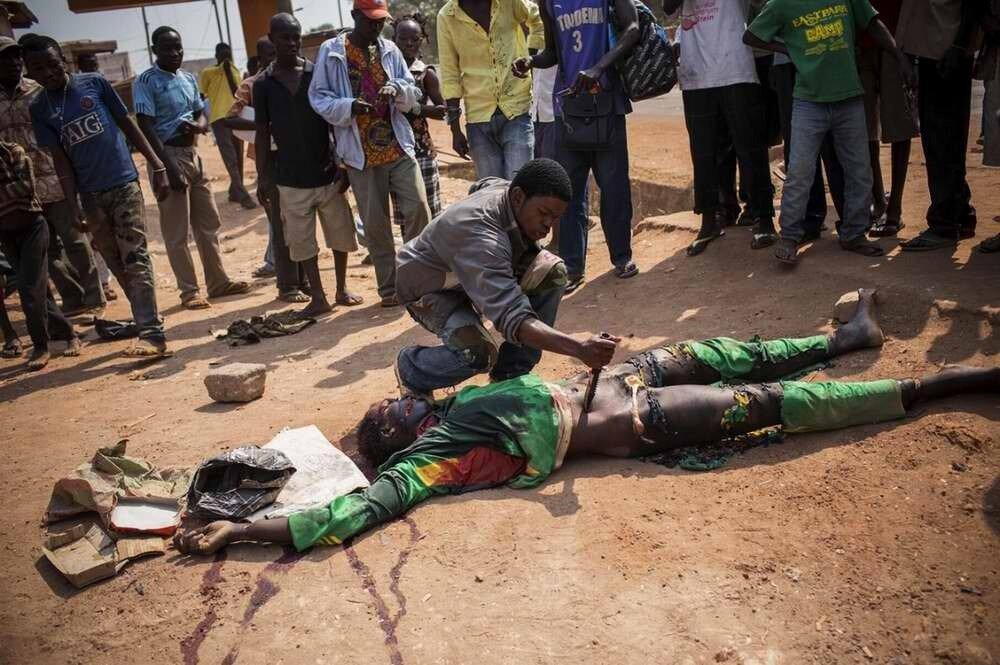 Местные жители с удовлетворением и радостью наблюдают за тем, как уличный боевик ножом кромсает тело только что убитого им мусульманина