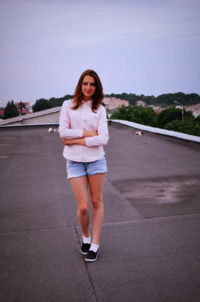 Девушка гуляет по крыше в рубашке и джинсовых шортах