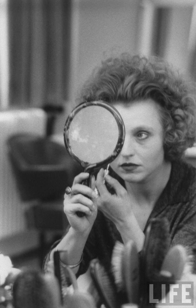 1980. Актриса Ханна Шигулла смотрится в зеркальце во время нанесения макияжа