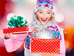 Surprised  woman with a christmas gift with magic shining from box