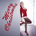 Full length side view of a blonde woman posing against a wall in very short and sexy Santa outfit.