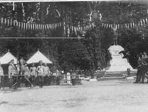 Почетный караул проходит церемониальным маршем мимо императора Николая II , стоящего возле царской палатки, и памятника шефу полка , великому князю Михаилу Николаевичу в день открытия памятника.