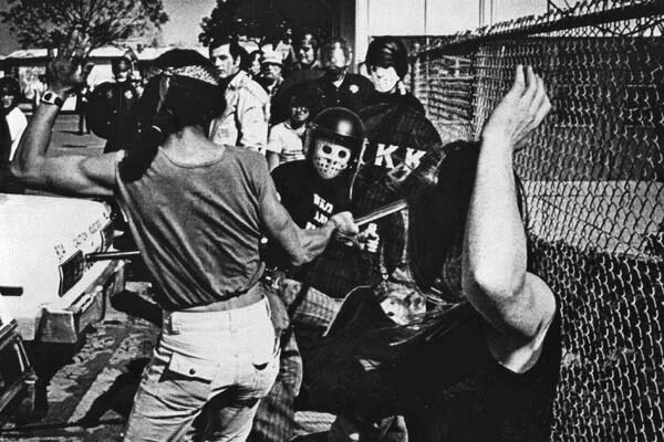 Mar. 15, 1980: Spectator gets into a fencing match with on of the KKK guards. The KKK man is using a billie club, the spectator, a plastic rod.  Fighting broke out at Ku Klux Klan rally in Oceanside, Calif.