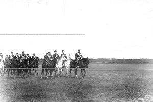 Император Николай II и сопровождающие его офицеры на военном поле.