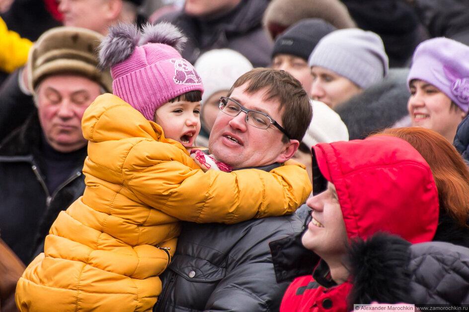 Девочка на руках у папы в толпе зрителей