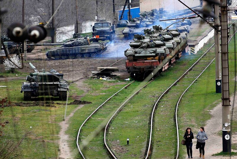 Local civilians walk at a train station in northern Crimea