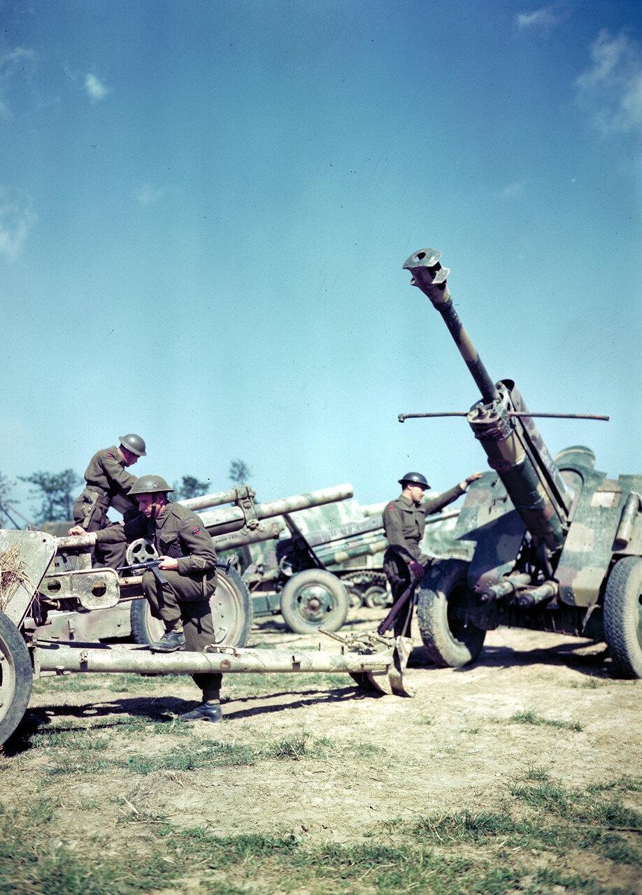 19. Канадские солдаты разглядывают немецкие трофейные орудия