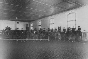 Группа всадников - офицеров бригады и дамы в помещении манежа.