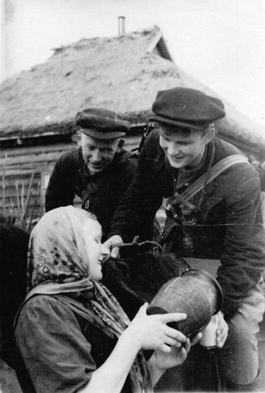 9-Колхозница угощает партизан - разведчиков молоком. ленингр. обл. 07-08.1942.jpg
