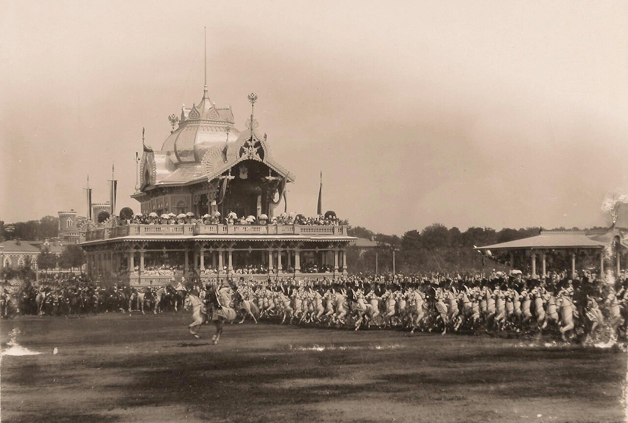 Прохождение гусарского полка церемониальным маршем во время парада на Ходынском поле мимо императорского павильона; справа - гостевая трибуна для лиц дипломатического корпуса