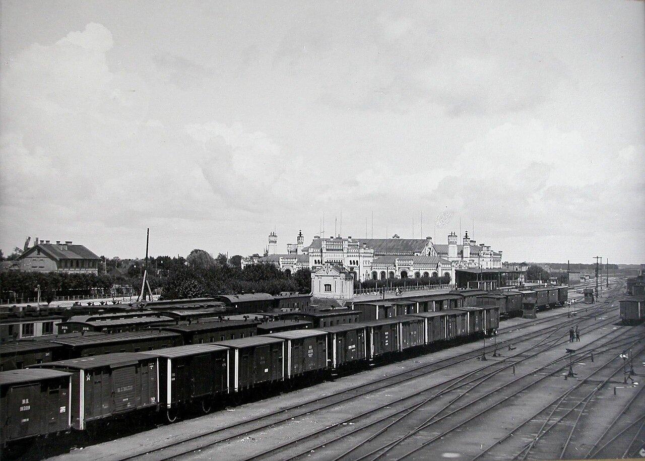Поезда на железнодорожных путях на станции; на втором плане - здание вокзала. 1900