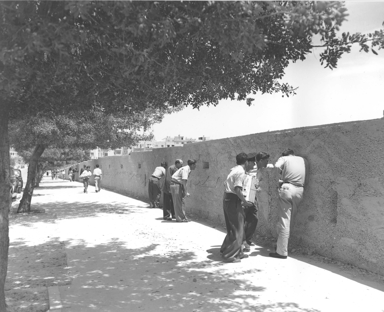 Евреи останавливаются вдоль проспекта Кинг-Джордж, чтобы посмотреть сквозь пробитые прорези в защитной стене в Иерусалиме, 17 мая