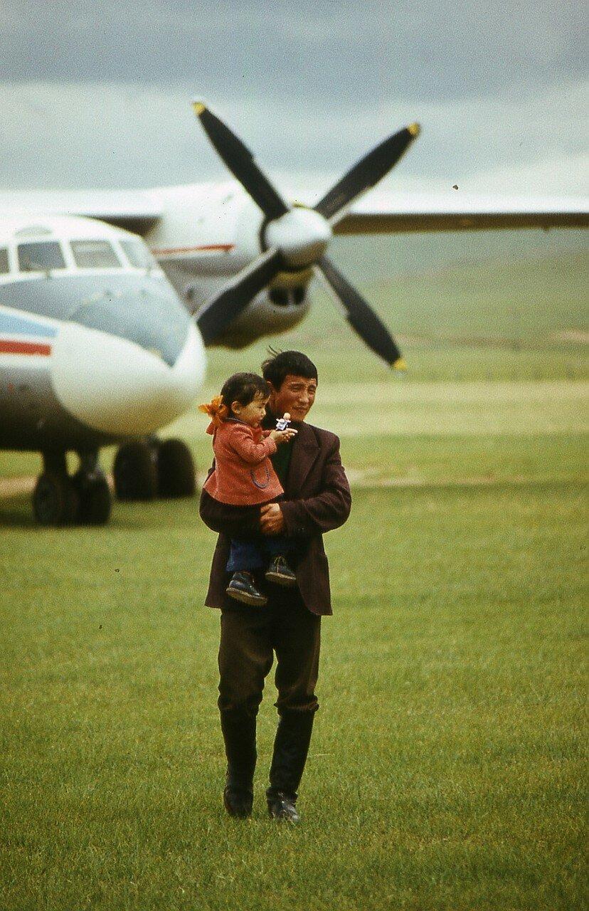 Человек с ребенком возле самолета в монгольской степи