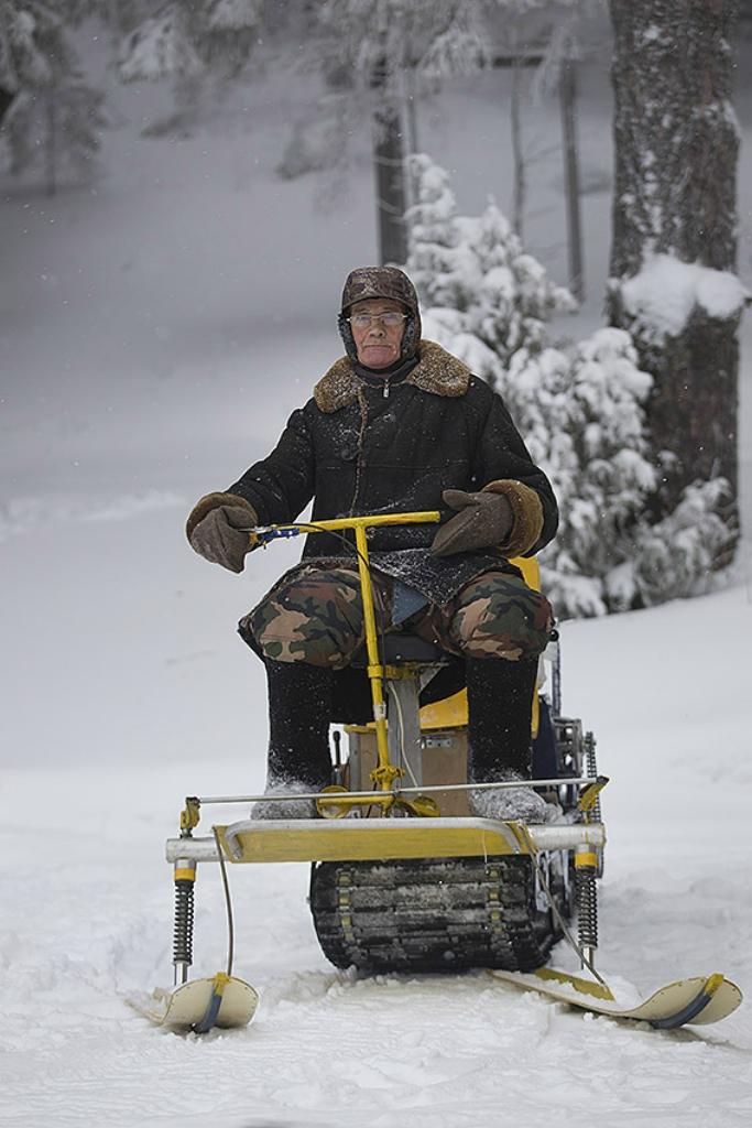 Снежный трактор выезжает из леса.