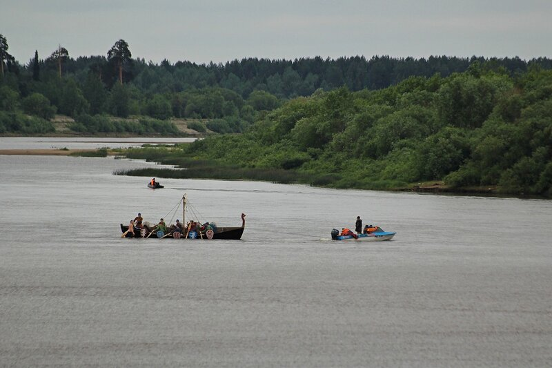 моторная лодка пытается буксировать севший на мель посреди Вятки новгородский ушкуй