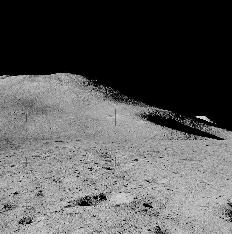 Надев гермошлемы и перчатки скафандров, астронавты через два часа после посадки начали так называемый «стоячий» выход из корабля. На снимке: Гора Хэдли Дельта и кратер Св. Георга. Снимок сделан Дэвидом Скоттом во время «стоячего» выхода